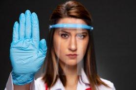 Vrouw met gezichtscherm op en blauwe handschoenen aan