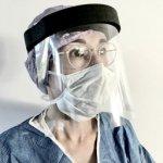 Transparant spatwaterdicht gezichtscherm met zwarte hoofdband van schuim, gedragen door vrouw in medisch schort en bril op